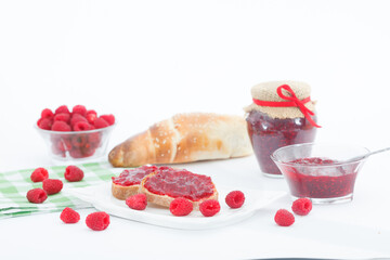 Breakfast with fresh roll and raspberry jam. Homemade raspberry marmalade in a jar with fresh fruit on white background.
