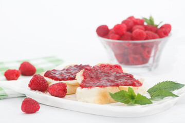 Raspberry jam with fresh raspberries and bread slices on white plate. Homemade marmalade, perfect for light, sweet breakfast.
