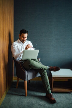 Elegant man using laptop while sitting in the armchair, portrait.
