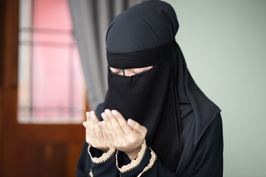 young modern middle eastern muslim woman with islamic prayer hand; concept of Ramadan, Eid al Fitr, meditation, islamic praying, islam festival, muslim religious activities