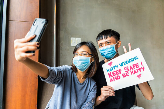 Asian girl and boy wearing a medical mask using smart phone video call conference camera and talking with their friends for happy wedding during COVID-19.