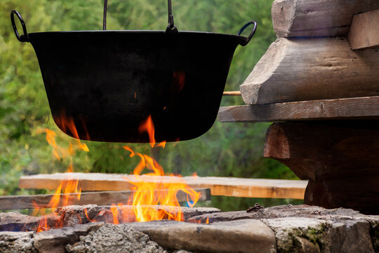 traditional hungarian bogracs goulash soup. cooking dish on open fire in a cauldron. preparing healthy food outdoors concept. popular european cuisine
