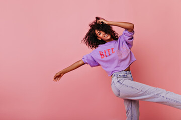 Beautiful shapely woman dancing with inspired face expression. Debonair black girl in purple shirt smiling on rosy background.