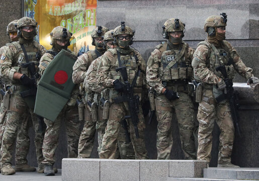 Members of the Security Service of Ukraine (SBU) stand outside a building where an unidentified man reportedly threatens to blow up a bomb in a bank branch, in Kyiv