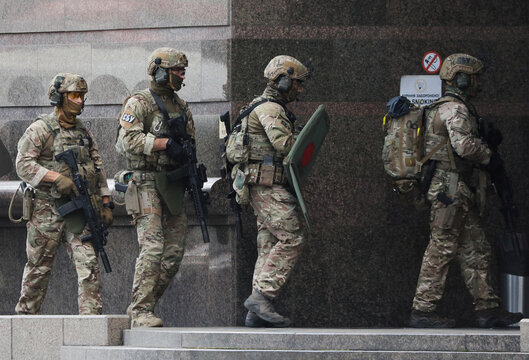 Members of the Security Service of Ukraine (SBU) enter a building where an unidentified man reportedly threatens to blow up a bomb in a bank branch, in Kyiv