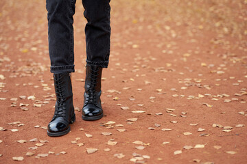 Woman's legs in fashionable autumn leather black boots and trendy black jeans. Trendy youth casual outfit for everyday. Modern street collection. Autumn road with yellow leaves on background.