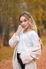 Autumn time. Closeup portrait of pretty confident young woman with long blonde hair wearing white shirt, black jeans, trendy autumn coat in autumn park.