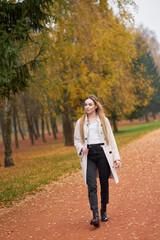 Look for every day. Pretty blonde young woman  wearing basic white shirt, black mom jeans, trendy autumn coat and stylish leather black boots walking in autumn park.