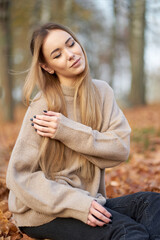 Closeup portrait of beautiful stylish blonde confident girl wth closed eyes and long blonde hair wearing cosy sweater sitting in autumn park.