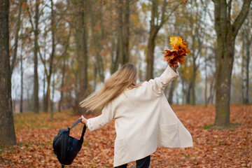 Love autumn. Happy stylish girl wearing trendy autumn coat, black mom jeans and leather black backpack holding bouquet of autumn leaves and have fun in the autumn park. View from back.