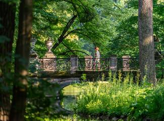 Romantischer Spaziergang am Nachmittag im Schlosspark - Frau geht über Brücke