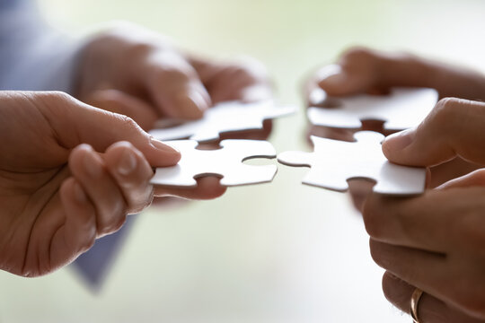 Close up hands of four businesspeople hold pieces of white puzzle, assemble jigsaw, put it together, joint path to problem solution, find way out exit of difficult situation. Support, teamwork concept