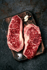 Two raw new York steaks on a chopping Board with seasonings and garlic. Wagyu meat for grilling,...