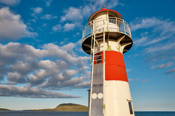 Red and white picturesque lighthouse. Faroe islands, Torshavn harbor