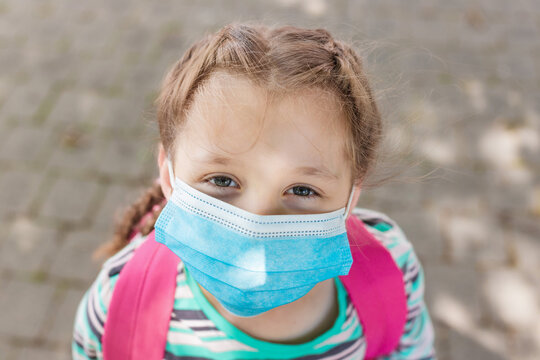 Close-up portrait of a school-age girl with a protective medical mask on her face. New school year in 2020. Protecting children during the coronavirus period in educational institutions