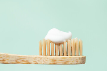 Bamboo toothbrush with toothpaste on mint background with copy space. Close up view in sunlight.