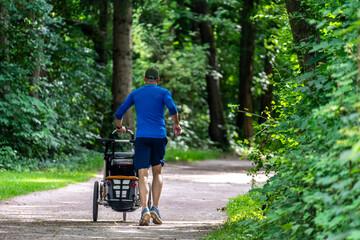 Joggen / Laufen in den Isar-Auen am Flaucher in München: Mann mit Lauf-Kinderwagen / Baby-Buggy beim Running