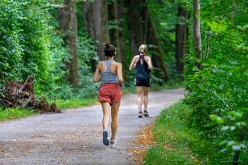 Joggen / Laufen in den Isar-Auen am Flaucher in München: aktive junge Frau beim Running