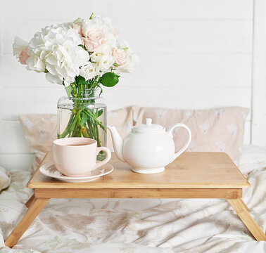 Breakfast in bed in hotel room. Accommodation. Breakfast in bed with tea cup and flowers on bed background top view. Copy Space. Romantic valentine's day breakfast. Cozy morning. Happy Mother's Day