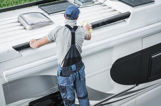 RV Service Worker Cleaning Camper Van Roof