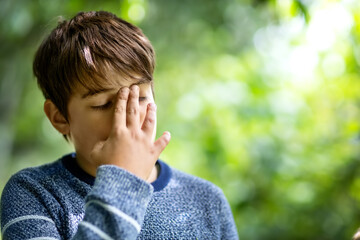 child with headache. Upset young boy outdoors