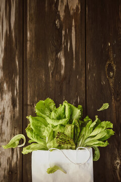 Lettuce leaveson in a paper bag a wooden dark table. Batavia salad. Authentic still life with green salad flat lay. Rustic style Top view