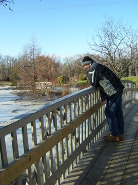 Senior man looking at the icy Spring river under a bridge in the park.
