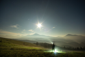 Silhouette of a man on a moonlit night in the carpathian mountains
