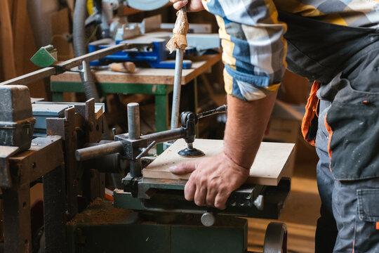 Carpenter using drilling machine on hardwood board