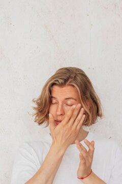 Tender male model applying cream under eyes