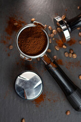 Portafilter with coffee and temper on table