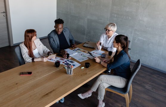 Inspired diverse coworkers at table project in minimalist office