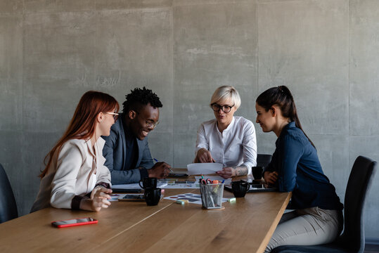 Diverse workers with boss exploring document