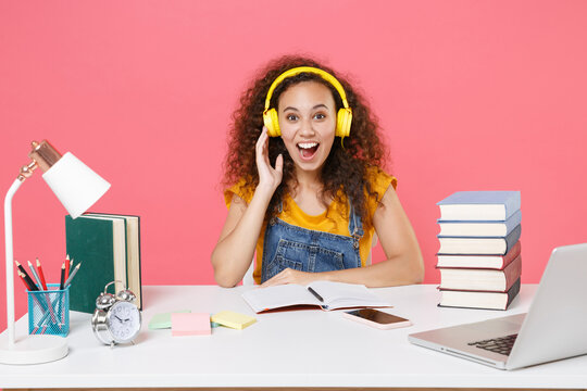 Excited african american girl employee in office work at desk isolated on pink background. Achievement business career. Education in school university college concept. Listen music with headphones.