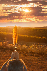 Man in ceremony holding feather at sunset with golden light