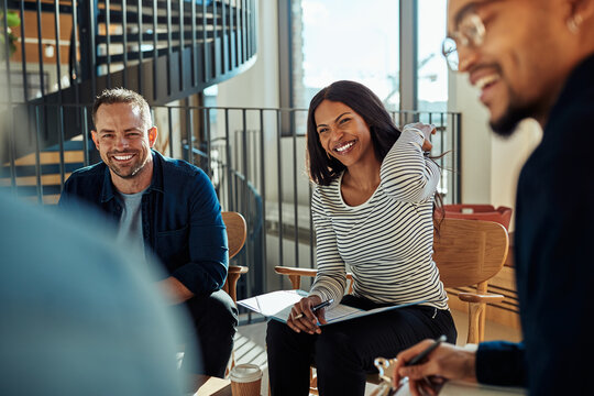 Group of diverse businesspeople laughing together in an office meeting