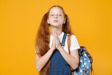 Young school girl 12-13 years old in white t-shirt blue denim uniform backpack hands folded in prayer isolated on yellow background children studio portrait Childhood kids education lifestyle concept