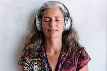 Grey hair natural style woman are listening music and posing in big hi-fi stereo headphones closeup portrait Papier Peint