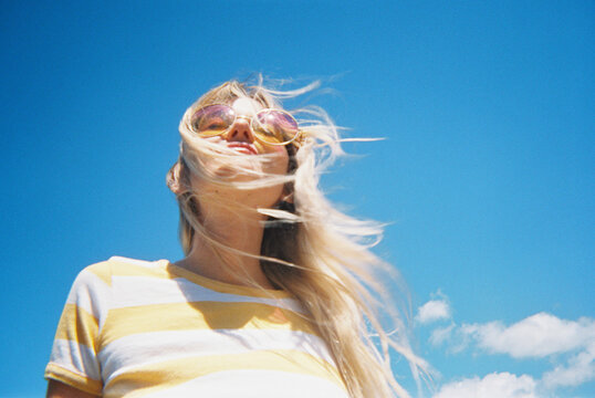 Blonde beautiful woman against bright blue sky in underwear and bra and striped tee