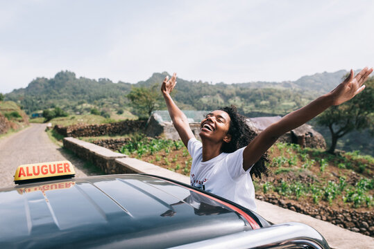 Happy ethnic female leaning out of car