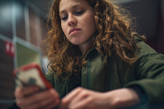 Portrait of teenage girl with curly hair and freckles indoors