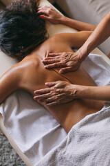 Masseur doing massage of female back indoor