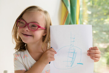 Little girl with down syndrome showing off artwork