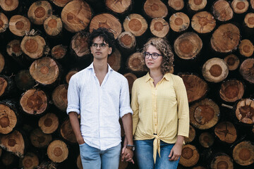 Young couple hand in hand in front of stacked wooden tree logs