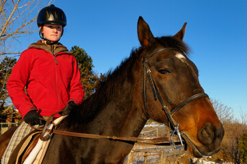 Fototapeta Young female rider in red jacket training her horse on a winter trail with a blue sky