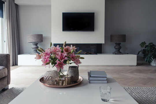 View from the couch of a modern living room with pink lilies on the coffee table