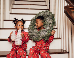 Family taking Christmas pictures on the stairs in matching pajamas