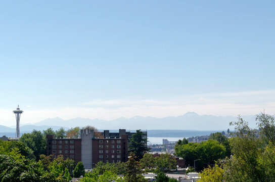 Panoramic view of the Olympic Mountain Range across from Seattle and partial view of a Seattle neighborhood with Space Needle on the left.