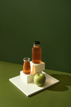 Fresh apple juice in the bottle on green background.