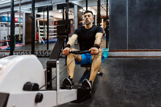Man Practicing Indoor Rower In The Gym.